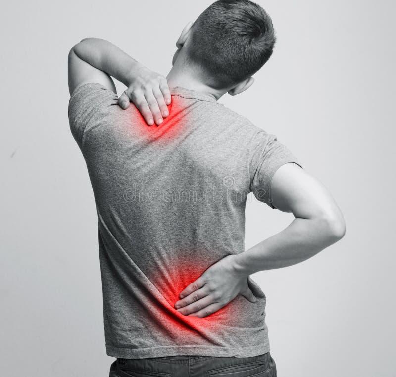 Mannen med halsen och baksida smärtar och att gnida hans smärtsamma kropp arkivfoto