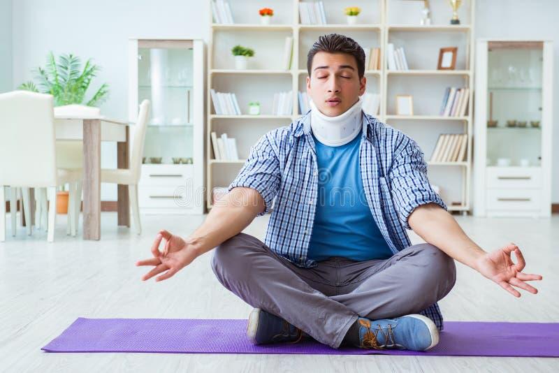 Mannen med halsskadan som hemma mediterar på golv royaltyfri bild