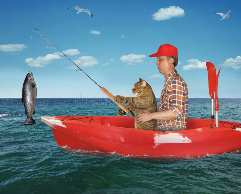 Mannen med hans katt fångade en fisk royaltyfria foton