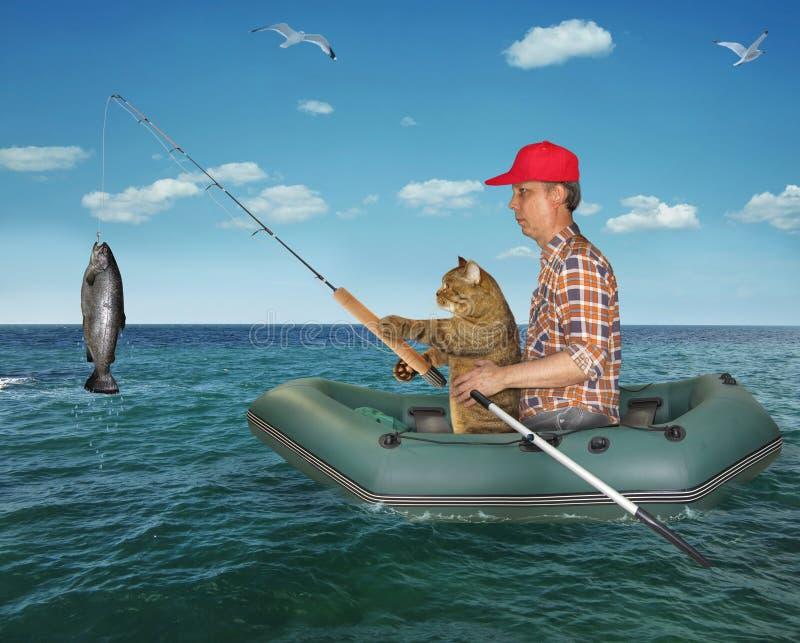 Mannen med hans katt fångade en fisk 2 fotografering för bildbyråer
