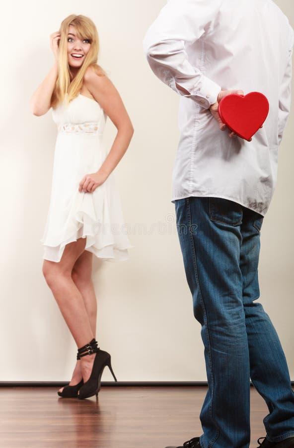 Mannen med hjärta formade gåvaasken för kvinna royaltyfri bild