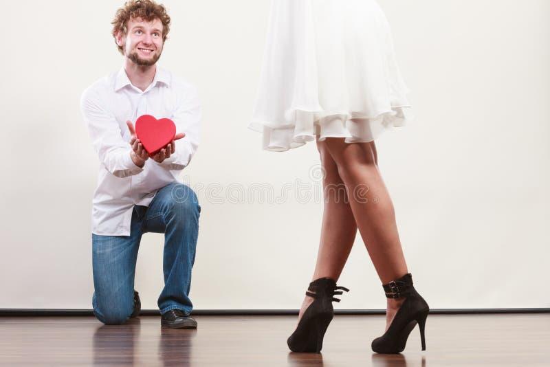 Mannen med hjärta formade gåvaasken för kvinna royaltyfria foton