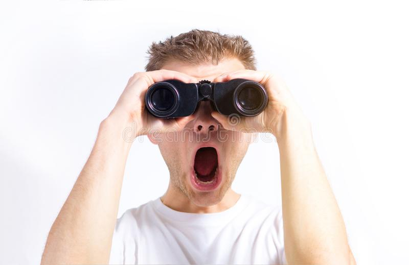 Mannen med kikare i händer på en vit bakgrund isolerade att se kameran royaltyfri foto