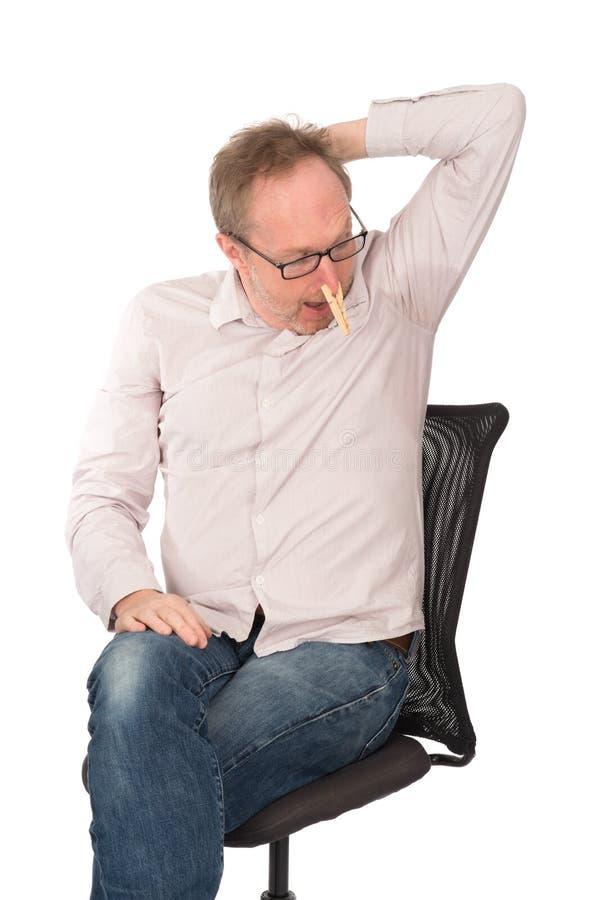 Mannen med klädnypan på näsa stirrar på hans svettigt Underarm royaltyfri foto