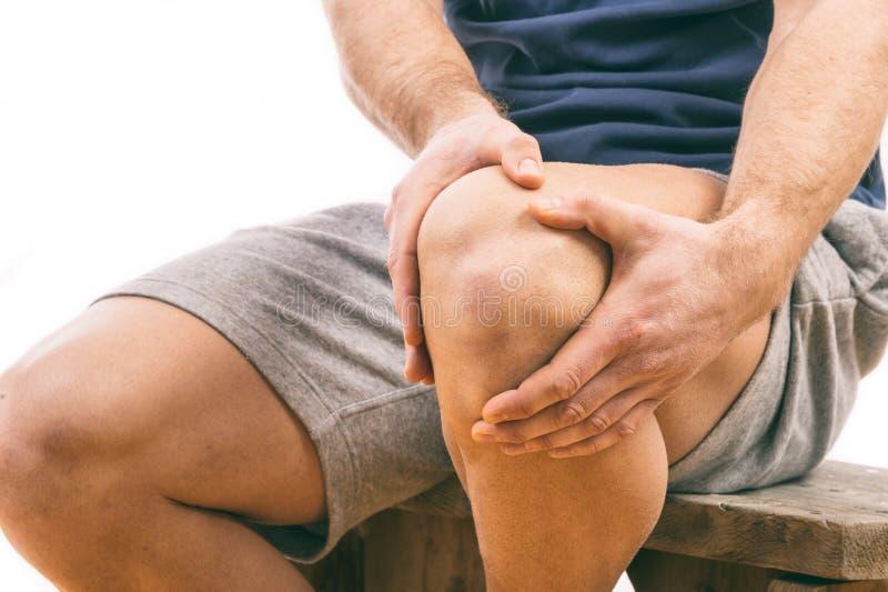 Mannen med knäet smärtar royaltyfria foton