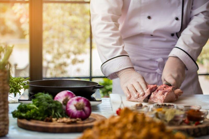 Mannen med kniven klipper kött fotografering för bildbyråer
