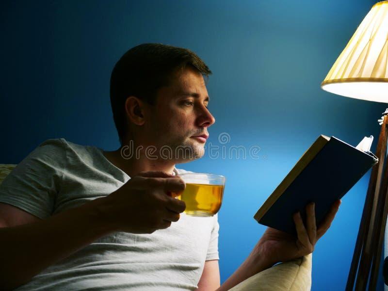 Mannen med kopp te är läseboken på aftonen royaltyfria foton