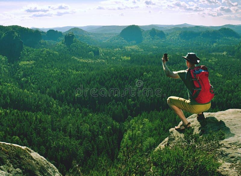 Mannen med lädercowboyhatten och den röda ryggsäcken sitter på toppmöte fotografering för bildbyråer