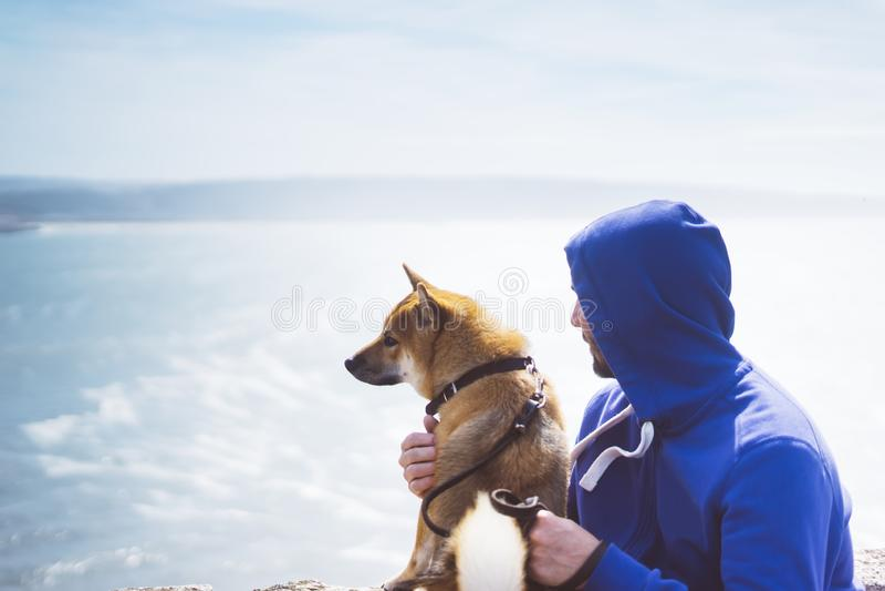 Mannen med liten guld- japansk samhörighetskänsla för sammanträde för shibainuhund på ett berg och att se den blåa havshorisonten royaltyfri foto