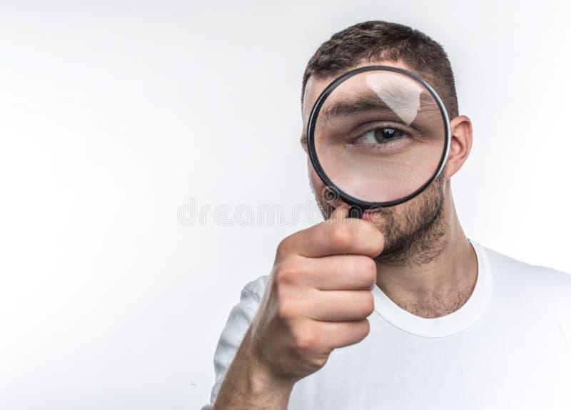 Mannen med loupen ser rak framåt och visar hans öga till och med exponeringsglaset Han är en utredare Isoolated på fotografering för bildbyråer