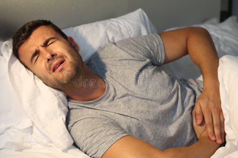 Mannen med magen smärtar lidande arkivbilder