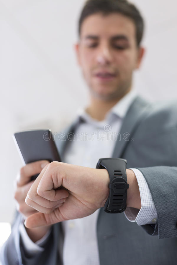 Mannen med mobiltelefonen förband till en smart klocka arkivbild