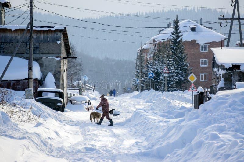 Mannen med rengöringar för en skyffel snöar på utkanten av byn på bakgrunden av bostads- byggnader arkivbilder
