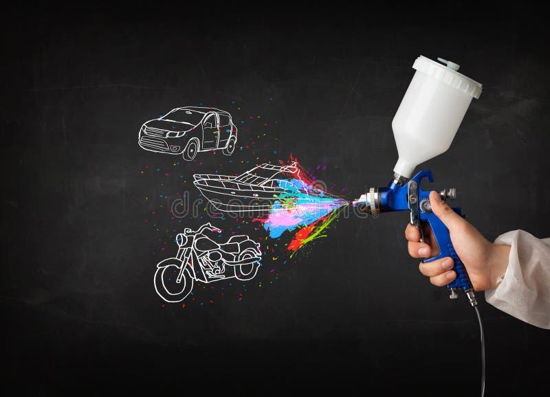 Mannen med retuschsprutasprutmålningsfärg med bilen, fartyget och motorcykeln drar arkivfoto