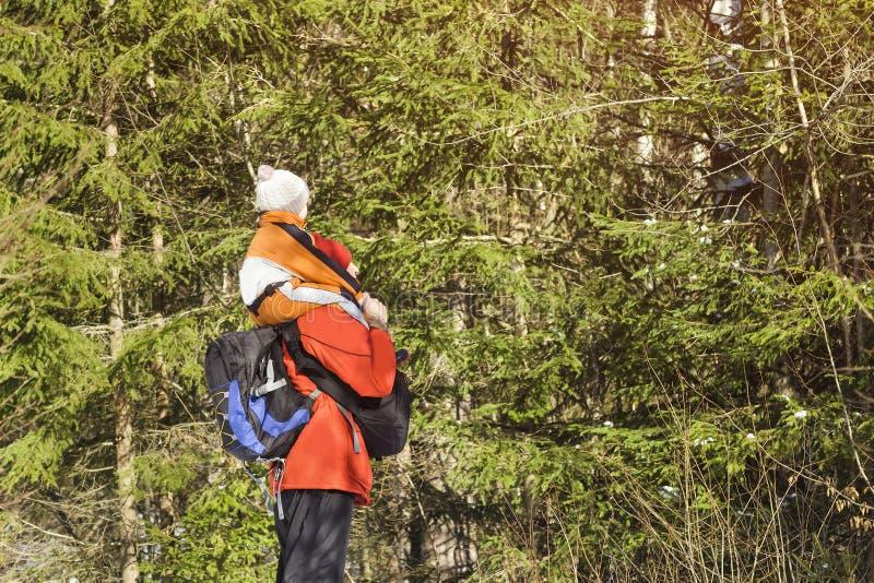 Mannen med ryggsäcken och sonen på skuldror står mot bakgrunden av barrträd i skogvinterdagen Slapp fokus arkivbild