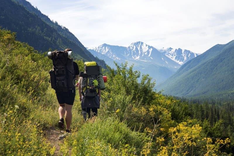 Mannen med ryggsäcken som fotvandrar i berg, reser sporten för aktiva semestrar för affärsföretaget för livsstilframgångbegreppet arkivbild