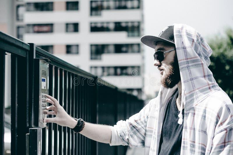 mannen med skägget i ljust rutigt omslag med huven i ett lock och solglasögon väljer upp lägenhetnumret på tangentbordet för att  royaltyfria bilder