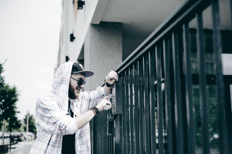 mannen med skägget i ljust rutigt omslag med huven i ett lock och solglasögon väljer upp lägenhetnumret på tangentbordet för att  arkivfoto