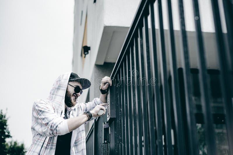 mannen med skägget i ljust rutigt omslag med huven i ett lock och solglasögon väljer upp lägenhetnumret på tangentbordet för att  arkivfoton