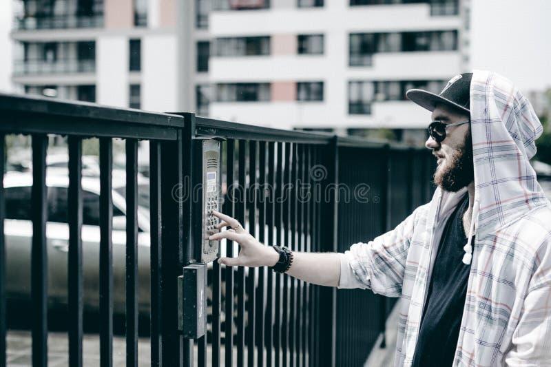 mannen med skägget i ljust rutigt omslag med huven i ett lock och solglasögon väljer upp lägenhetnumret på tangentbordet för att  fotografering för bildbyråer
