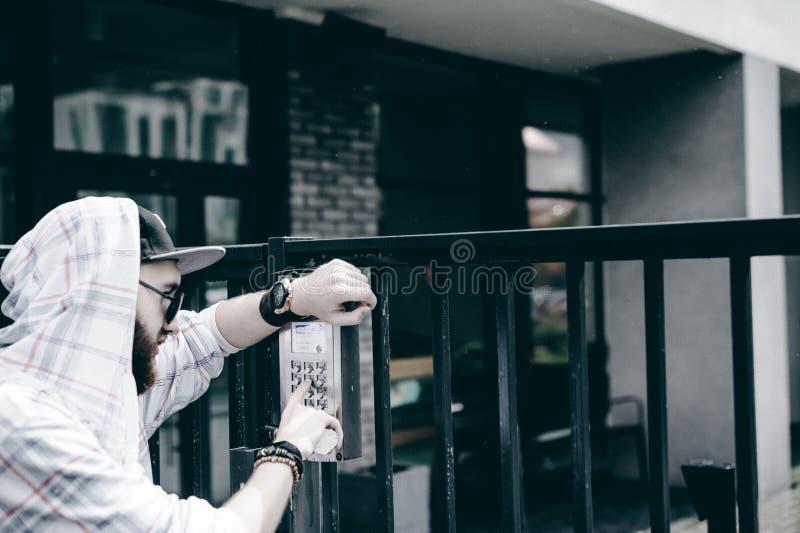 mannen med skägget i ljust rutigt omslag med huven i ett lock och solglasögon väljer upp lägenhetnumret på tangentbordet för att  royaltyfri foto