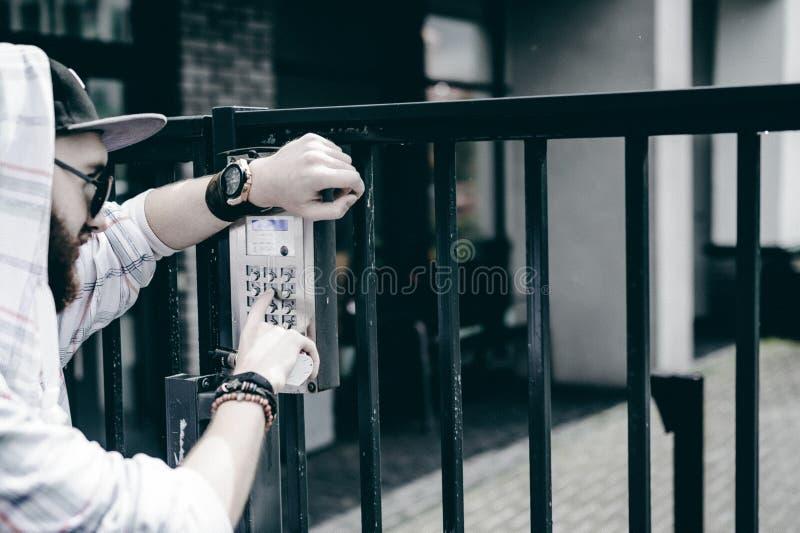 mannen med skägget i ljust rutigt omslag med huven i ett lock och solglasögon väljer upp lägenhetnumret på tangentbordet för att  royaltyfria foton