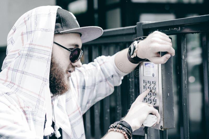 mannen med skägget i ljust rutigt omslag med huven i ett lock och solglasögon väljer upp lägenhetnumret på tangentbordet för att  arkivbilder