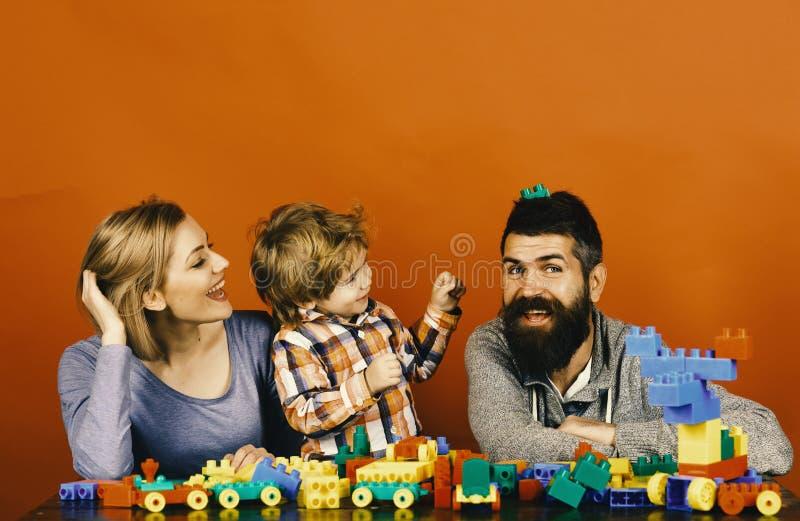 Mannen med skägget, kvinnan och pojken spelar på röd bakgrund Dagis- och familjbegrepp Föräldrar och unge i lekrum arkivfoto