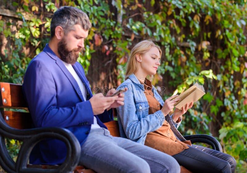 Mannen med skägget och kvinnan läste alternativ informationslagring Läs- hobbybegrepp Den lästa boken parkerar in angenäm fritid fotografering för bildbyråer