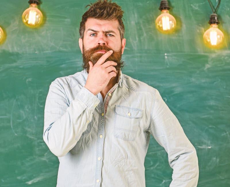 Mannen med skägget och mustaschen på fundersam framsida står framme av den svart tavlan Intellektuellt uppgiftsbegrepp Tänka för  arkivfoton