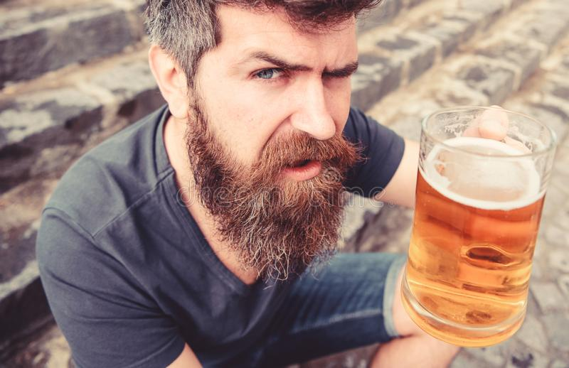 Mannen med skägget och mustaschen rymmer exponeringsglas med öl, medan sitter på stentrappa som är defocused Grabb som upp lyfter arkivfoto