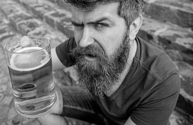 Mannen med skägget och mustaschen rymmer exponeringsglas med öl, medan sitter på stentrappa som är defocused Grabb som upp lyfter royaltyfri foto