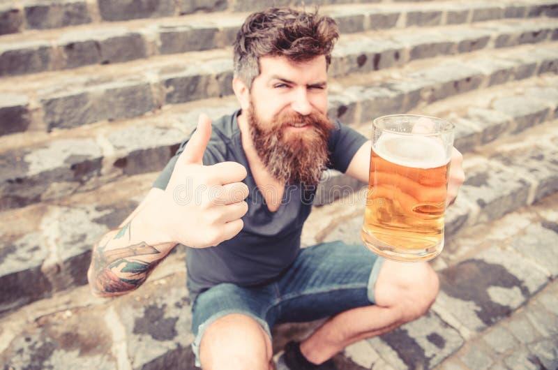 Mannen med skägget och mustaschen rymmer exponeringsglas med öl och visar upp tummen, stentrappabakgrund Grabben som den har, vil royaltyfria bilder