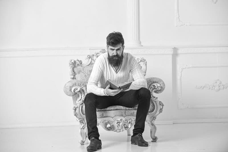 Mannen med skägget och mustaschen sitter på fåtöljen och läseboken, vit väggbakgrund Forskare professor på allvarligt arkivfoto
