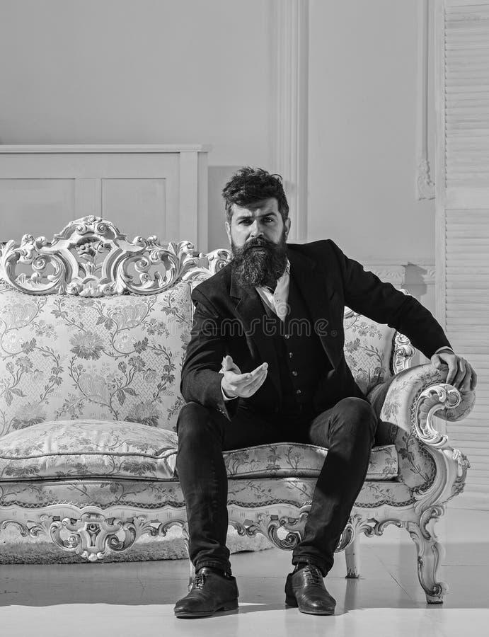 Mannen med skägget och mustaschen som bär den trendiga klassiska dräkten, sitter på den gammalmodiga soffan eller soffan Dana och royaltyfri foto