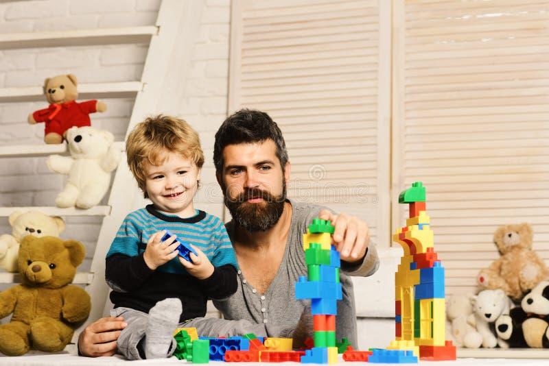 Mannen med skägget och pojken spelar på wood väggbakgrund royaltyfria bilder