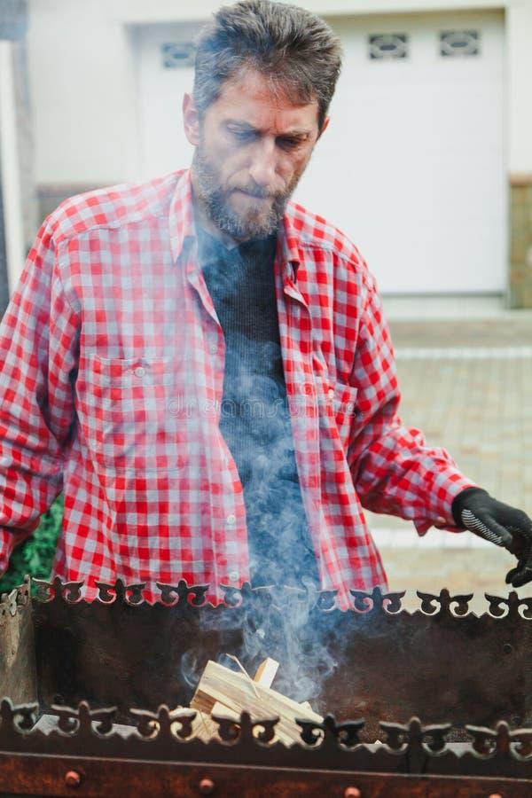 Mannen med skägget sätter vedträ i brandmangala royaltyfri foto