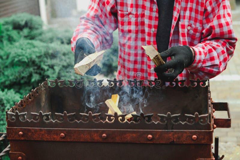 Mannen med skägget sätter vedträ i brandmangala royaltyfri fotografi