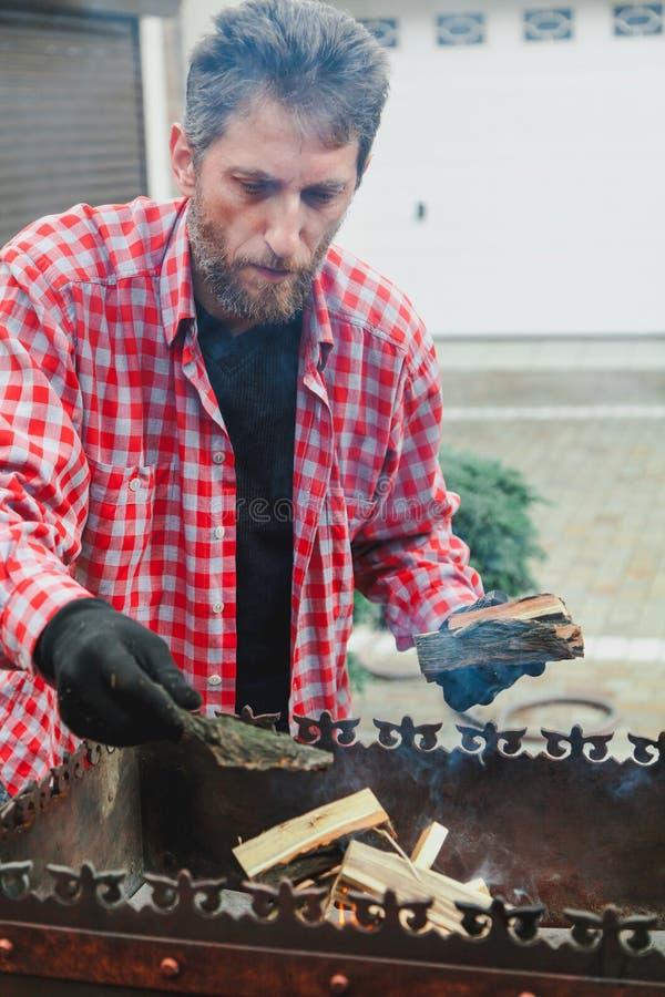 Mannen med skägget sätter vedträ i brandmangala arkivbilder
