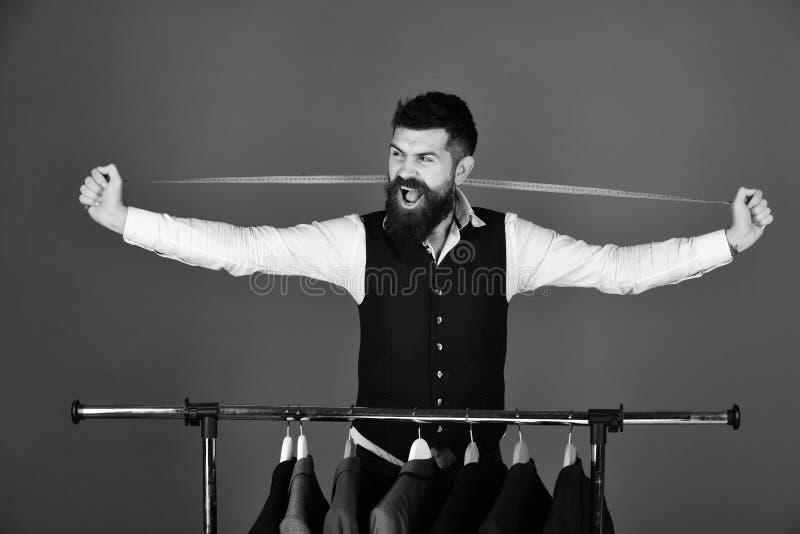 Mannen med skägget tar mått vid kläderkuggen med dräkter royaltyfria foton