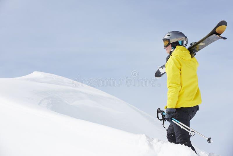 Mannen med skidar på ferie i berg royaltyfria bilder
