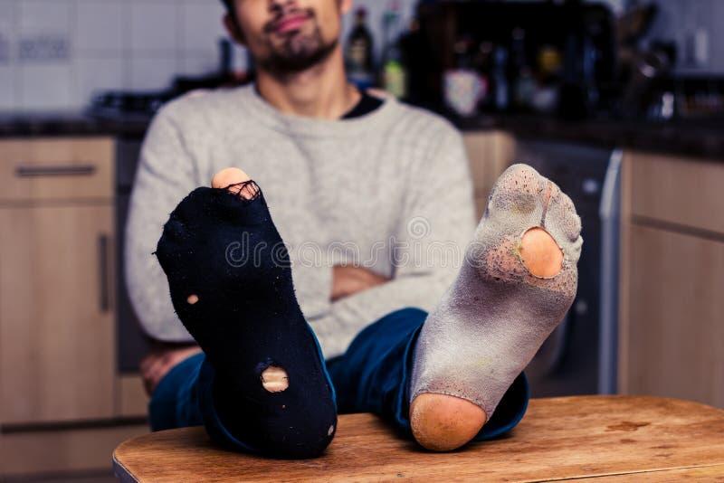 Mannen med slitet slår ut att koppla av i kök fotografering för bildbyråer