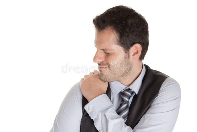 Mannen med smärtar i hans skuldramuskler som isoleras på vit bakgrund arkivbild