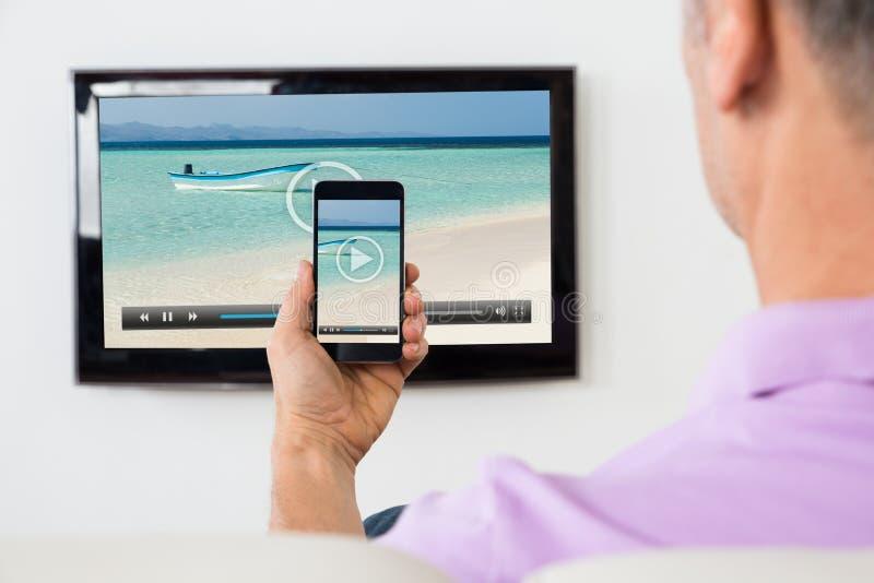 Mannen med Smartphone förband till en hållande ögonen på video för TV royaltyfri fotografi