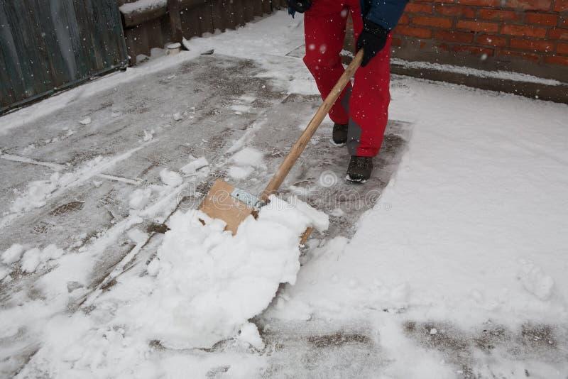 Mannen med snöskyffeln gör ren utomhus i vinter arkivbilder