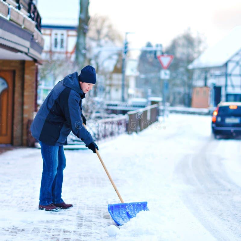 Mannen med sn?skyffeln g?r ren trottoarer i vinter under sn?fall Vintertid i Europa Ung man i varm vinterkl?der arkivfoto