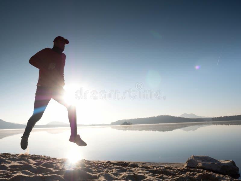 Mannen med solglasögon, den röda baseballmössan och den röda svarta sportswearen är köra och öva på stranden arkivfoton