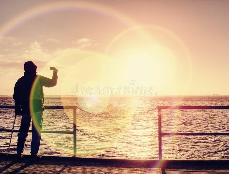 Mannen med telefonen i hand tar fotoet av soluppgång på vågbrytare för färjaport fotografering för bildbyråer