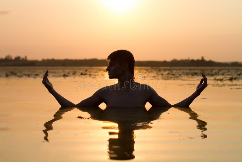 Mannen mediterar i vatten i strålar av solen arkivfoto