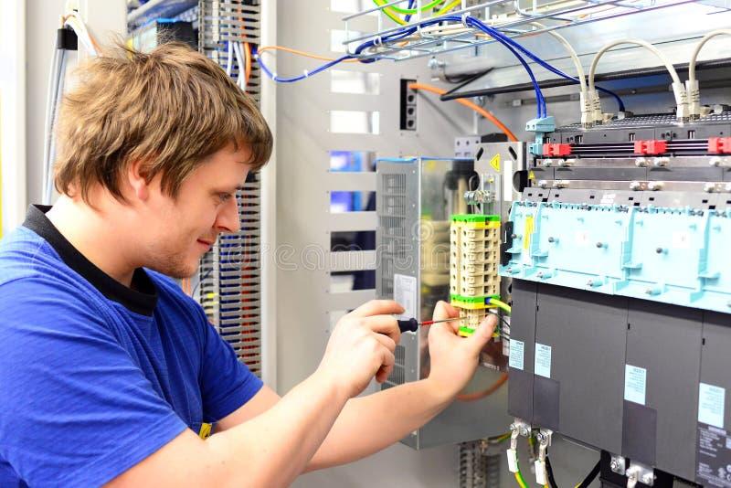 Mannen monterar elektroniska delar på en maskin i en fabrik fo fotografering för bildbyråer